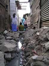 Dr Mune making visit to girls in slum