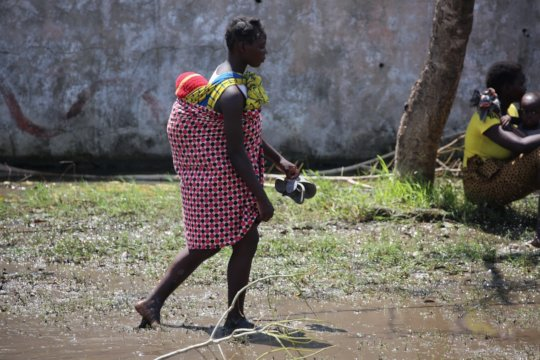 Carrying a child across the flooded areas.