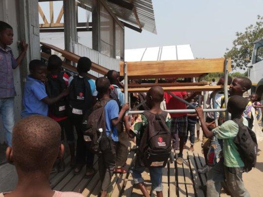 Scholars Assist by Offloading New Desks