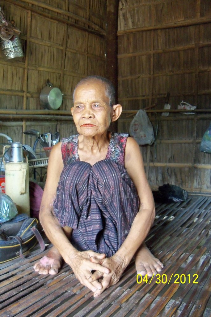 Grandmother, 85, sits inside the one room house.