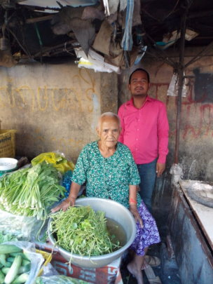 R, 26 with his grandmother at their market stall