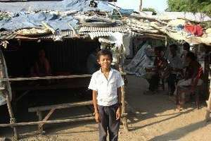 Kry,age 10, outside his home in Anlung Kgang