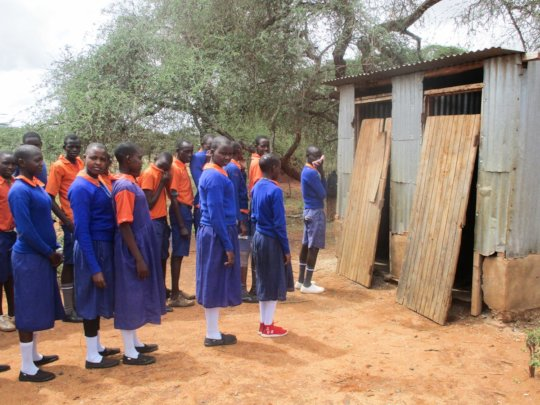 Students in East Africa line up to use latrines