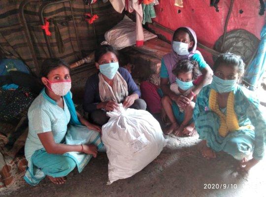 Families receiving food rations in New Delhi