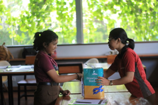 Volunteer hand in donation to sponsored student
