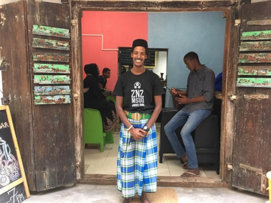 Our student, Feisal, in front of his juice shop