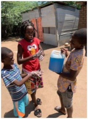 Children using sanitation gel made by the women.