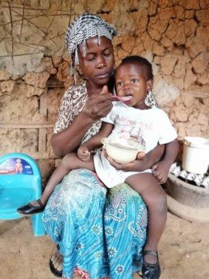 Afia feeding her daughter porridge.