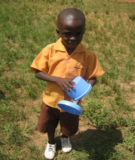 Kofi, a pupil, carrying his bowl.
