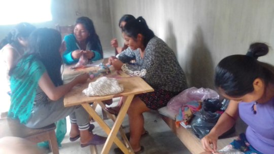 Young women embroidering and weaving