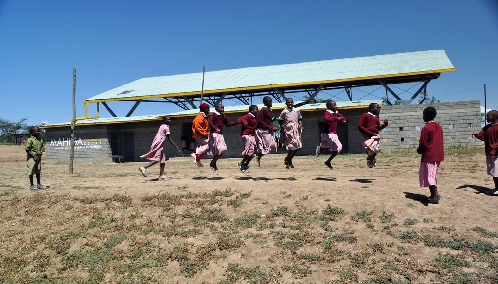 Seven Girls jumping rope in front of the RainWater Court at Mahiga Hope High School, the area