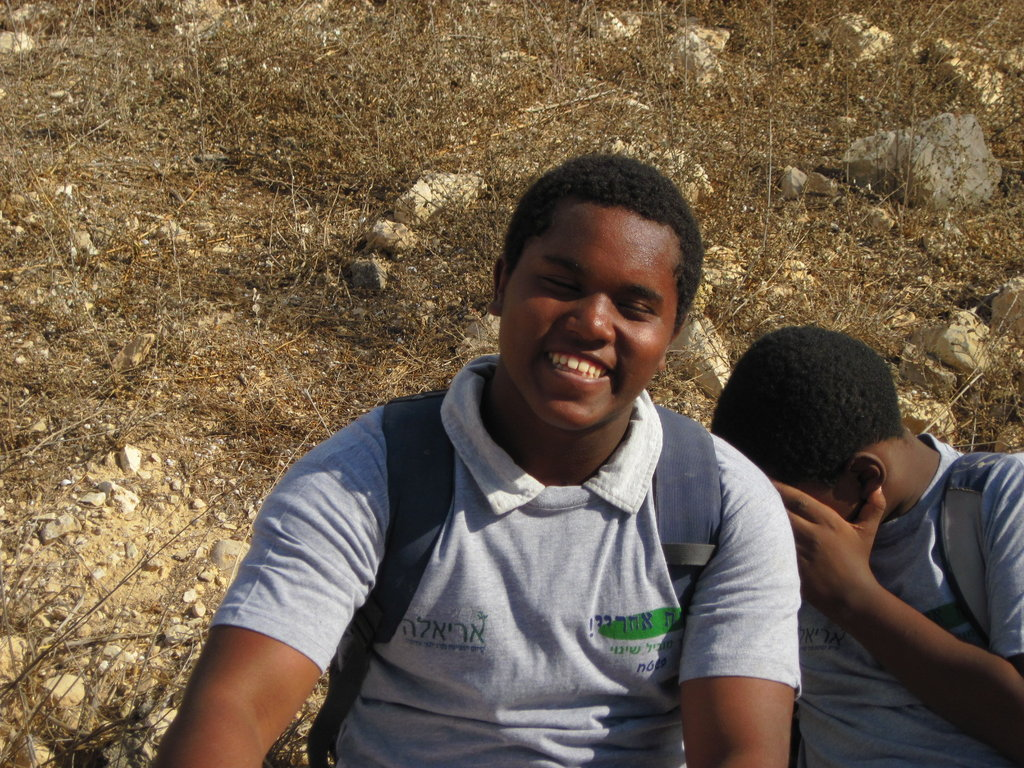 A program participant smiles during an overnight hiking field trip