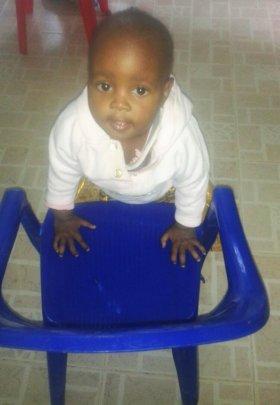 Fidelis using a plastic chair to walk around