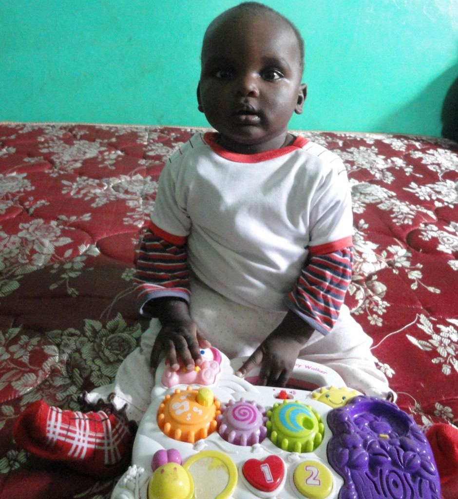 Baby Baraka can sit and play with his toy
