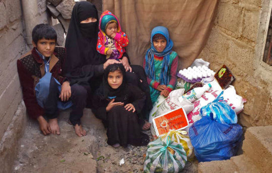 Yemeni family with their emergency food supplies.