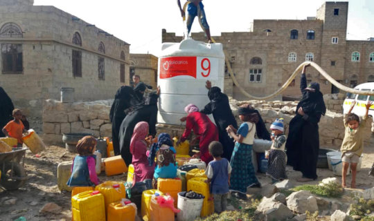 Women & children gather as water tanks are filled.