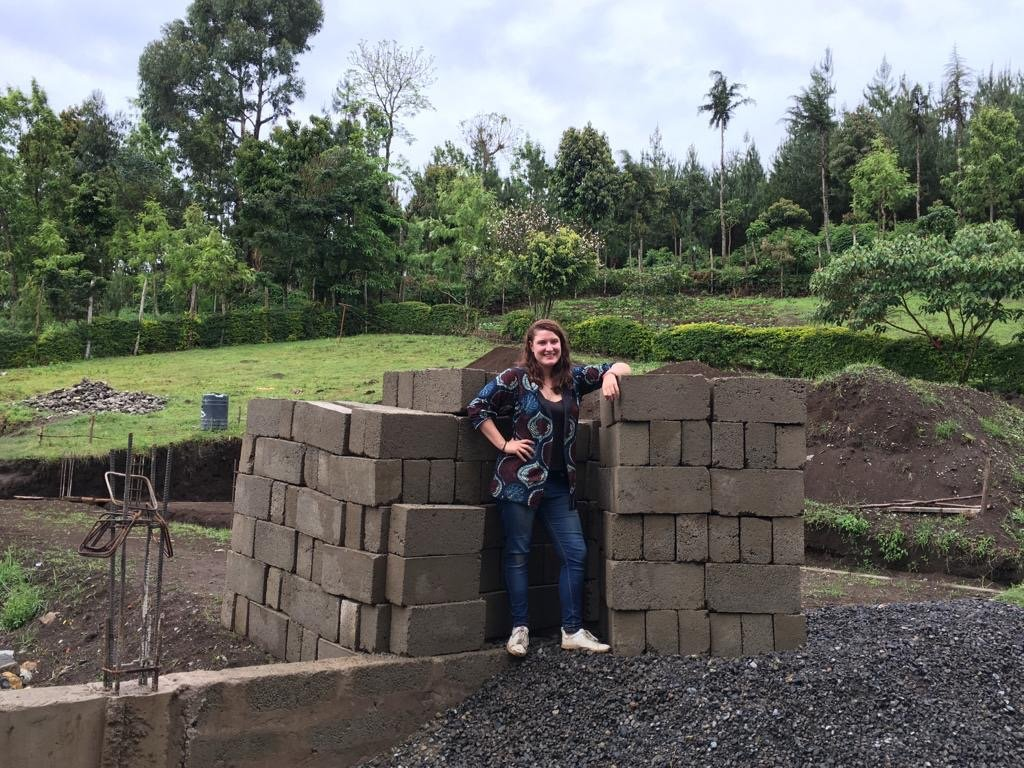 Volunteer with a load of bricks she donated