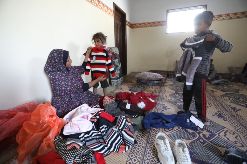 Om Adel dressing her children in new, warm clothes
