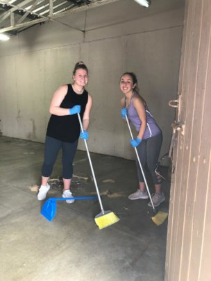 Volunteers sweeping in the Moises School