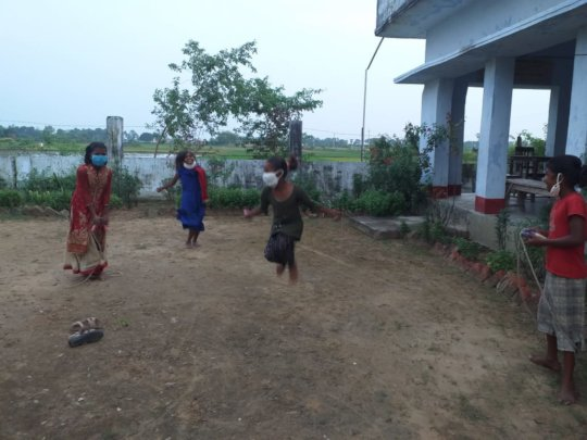 The girls enjoy skipping rope while at school.
