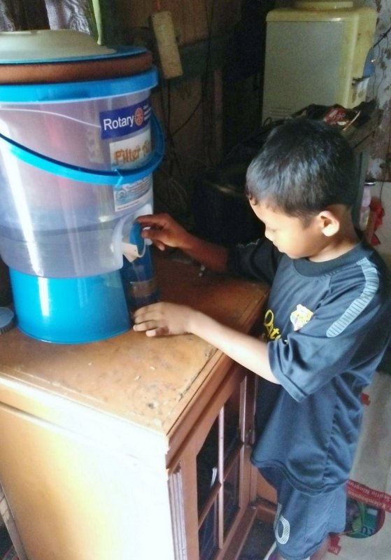 Deden helps his mom keep the water filter clean