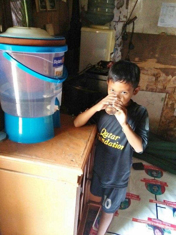 Deden helps mom clean the water filter