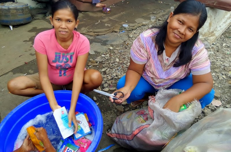 Supena and her sister, preparing trash to sell