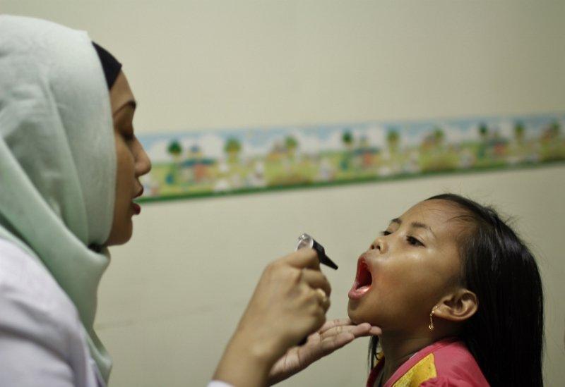 A nurse checks  for tonsillitis.