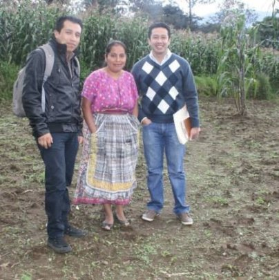Marta in her potato field with loan supervisors.