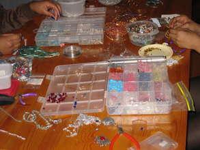 Girls creatiing jewelry at a FAIR Fund workshop