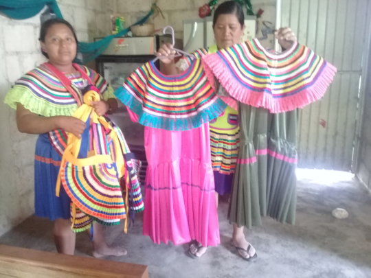 Women show their work in traditional dresses
