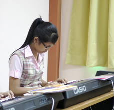 Kuch learning piano at school in Phnom Penh