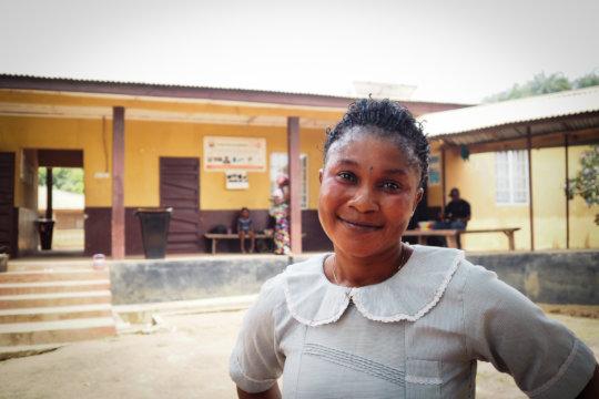 Asha outside Kagbere Health Centre