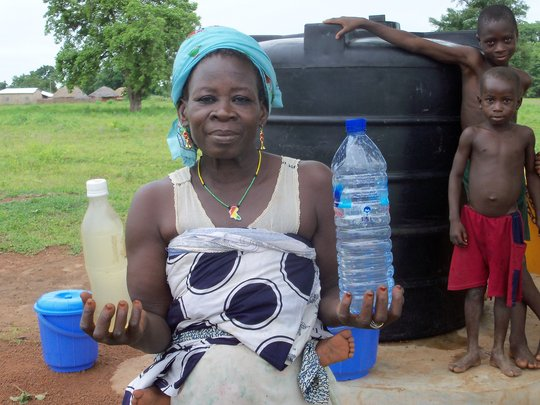 Abiba Fusheni holding the dugout water on the left