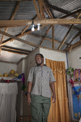 Justin Ibrahim showing the solar lights in a home.