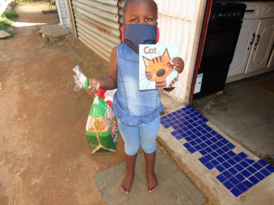 Supporting this child with a mask, book and bread