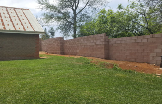 Completed section of wall behind a village house.