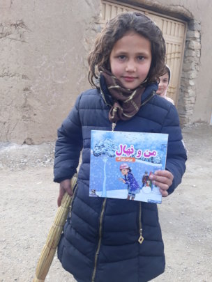 Happy young girl displaying the book she received