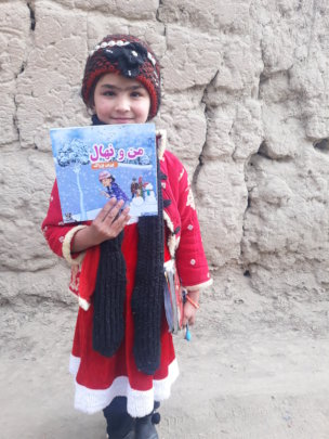 Happy young girl with the book, Kapisa province