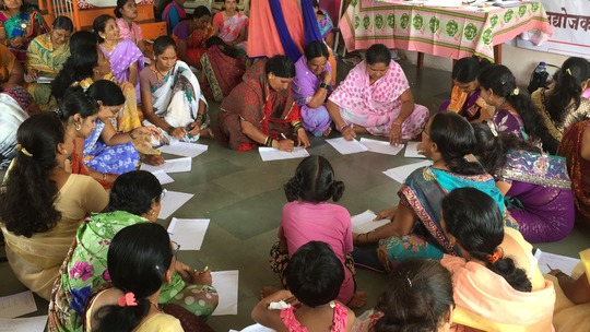 """Women in the group discussion writing ,""""who am I?"""""""