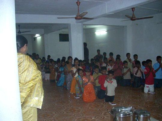 children praying in the dining hall