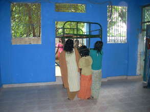 Children bring cots in to the new room
