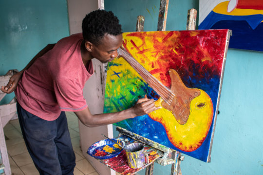 Uweza artist Kelvin working on a new piece