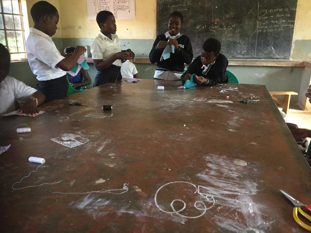 Girls at Minga learning how to make reusable pads