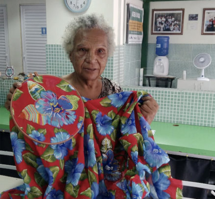 Maria Lucia with a sample of her embroidery