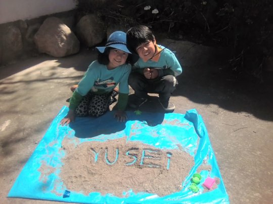 Y. and his little sister S. writing their names