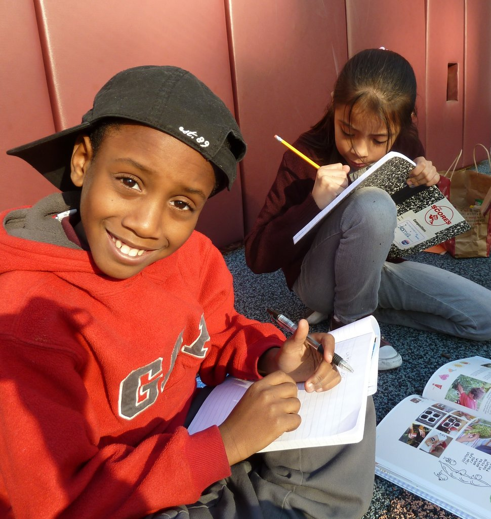 A Thomson Elementary School poet-athlete demonstrates the joy and enrichment that students within our program gain from working on service-learning projects each spring. In this picture, the pair of students is coming up with ideas for Thomson