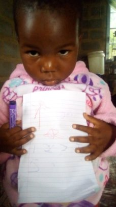Tiny Tot Showing off her Learning at Home work