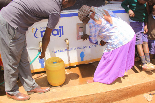 Community woman taps the e-payment token for water