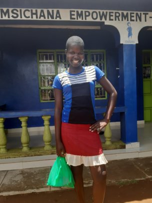 a girl collecting menstrual kit from our office